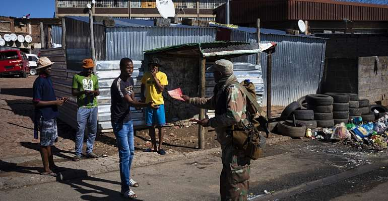 A member of the South African National Defence Force hands out pamphlets informing township residents about COVID-19 in Johannesburg.  - Source: Kim Ludbrook/EPA-EFE