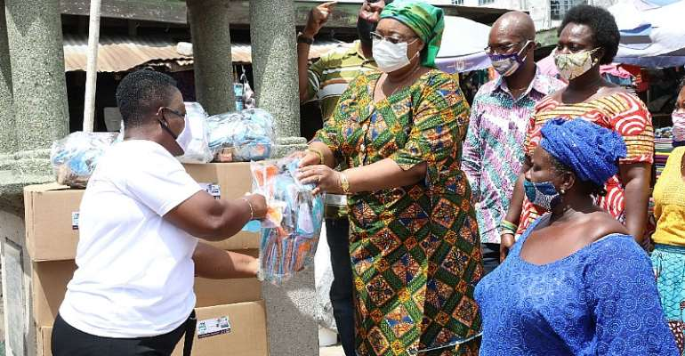 Mrs Amoah presenting the facemask and sanitizers to the market women.