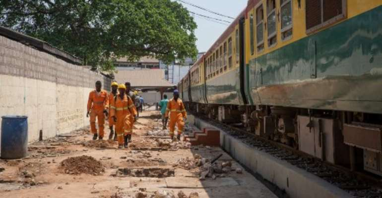 Maintenance staff walk along the railway line that connects the Ghanaian capital Accra and the city of Tema. The 25-kilometer route reopened in late January 2020 after rehabilitation.