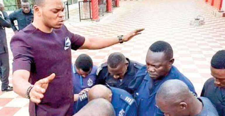 Daniel Obinim praying for some police officers