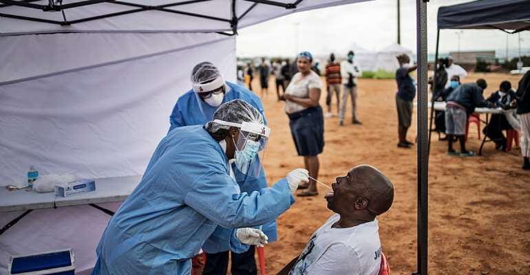 A healthcare worker collecting a swab for a COVID-19 test from a community member.  - Source: AFP via Getty Images