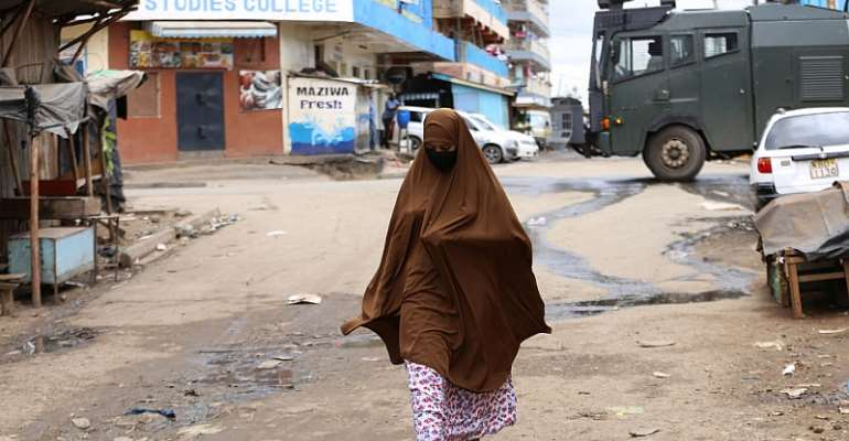 """A woman walks past a police armed vehicle in Eastleigh - Nairobi's """"little Mogadishu"""" - Source: Photo by Billy Mutai/SOPA Images/LightRocket via Getty Images"""