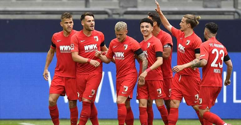 Eduard Loewen of Augsburg celebrates with teammates after scoring their sides first goal during the Bundesliga match between FC Schalke 04 and FC Augsburg at Veltins-Arena on May 24, 2020 in Gelsenkirchen, Germany.