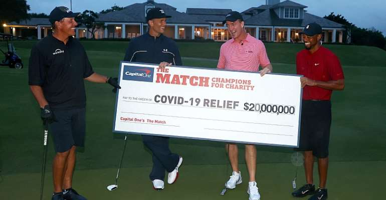 Photo caption:  HOBE SOUND, FLORIDA - MAY 24: Tiger Woods and former NFL player Peyton Manning celebrate defeating Phil Mickelson and NFL player Tom Brady of the Tampa Bay Buccaneers on the 18th green during The Match: Champions For Charity at Medalist Golf Club on May 24, 2020 in Hobe Sound, Florida. (Photo by Mike Ehrmann/Getty Images for The Match)