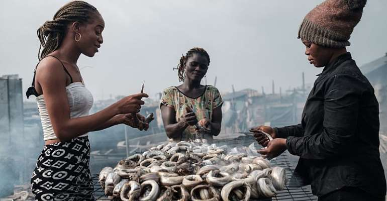 Women make smoked fishes - locally called Okporoko - at Egede informal settlement in Port Harcourt, Nigeria. - Source: YASUYOSHI CHIBA/AFP via Getty Images