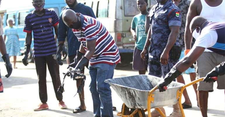Samuel Atta-Akyea de-silting a gutter