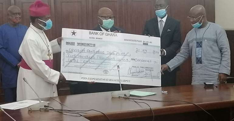 Archbishop Justice Ofei Akrofi receiving the dummy cheque from thw speaker of parliament