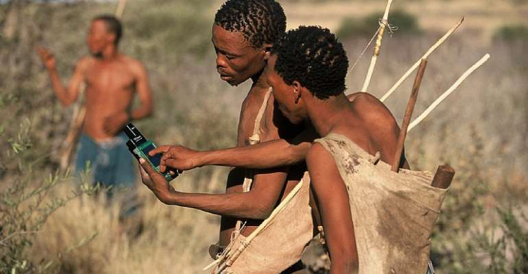 Karoha Langwane (right) teaching a tracker to collect data on a CyberTracker PDA/GPS device.  - Source: Rolex/Eric Vandeville