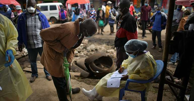 A public health worker takes details from a man volunteering to be tested for COVID-19 in the bustling Kawangware market in Nairobi.  - Source: Tony Karumba/AFP via Getty Images