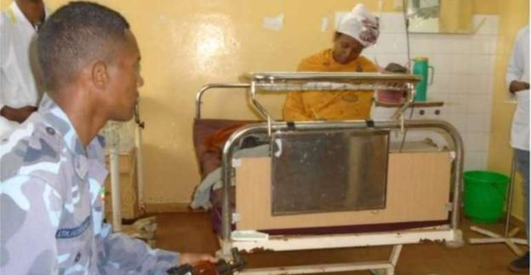 An Ethiopian woman writes exams on a hospital bed