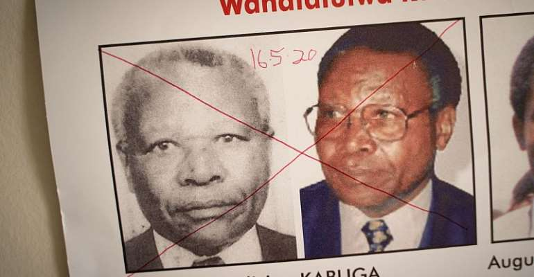 The date of arrest and a red cross marked on the face of Felicien Kabuga on a wanted poster at the Genocide Fugitive Tracking Unit office in Kigali, Rwanda, on May 19, 2020.  - Source: (Photo by Simon Wohlfahrt/ AFP via Getty Images)