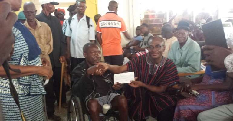 Gerald Atuogya presenting a cheque to a benefiary