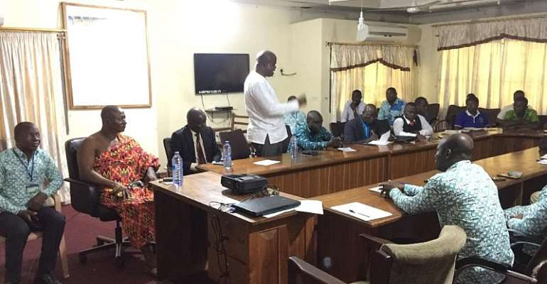 MR. MENSAH (STANDING) MAKING A POINT AT THE MEETING