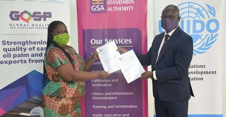 Abena Safoa Osei, Chief Technical Advisor & National Coordinator/ Global Quality and Standards Programme – Ghana with Prof. Alex Dodoo, GSA Director-General, displaying copies of the standards