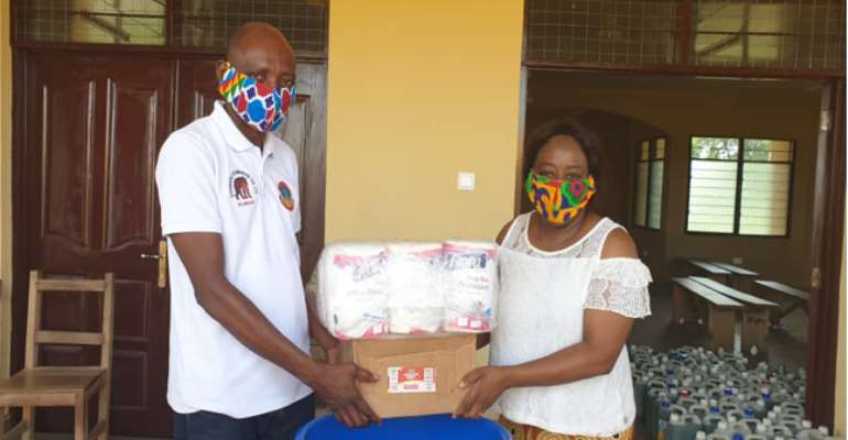 Madam Charity A.F. Dwommoh (DCE) Handing Over The Items To Mr. Mark Domah, Education Director