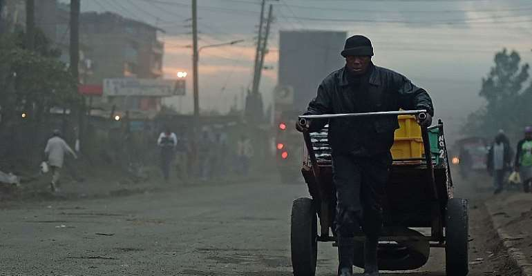 A man pulls a cart through the early morning smog in Nairobi. - Source: TOBIN JONES/AFP via Getty Images