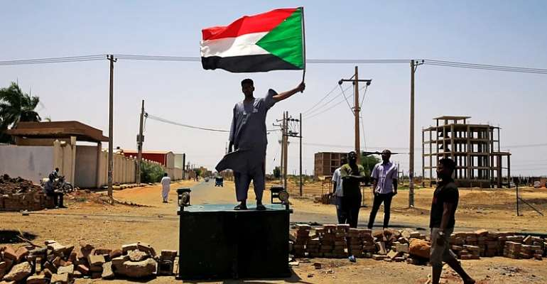 A protester in the city of Khartoum with a flag of Sudan