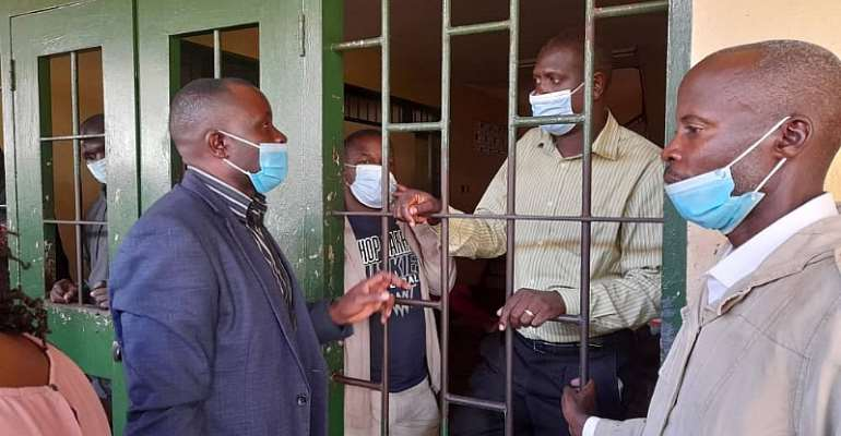 Journalists Darious Magara (in jail cell, left) and Pidson Kareire (in jail, right) are seen with Robert Ssempala (left), the executive director of the Human Rights Network for Journalists-Uganda, while in detention on criminal libel charges. (Photo: HRNJ-U)