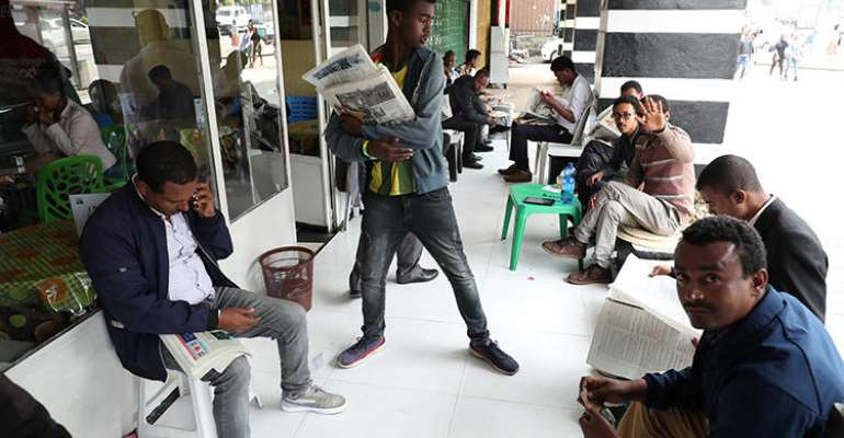 Ethiopians read newspapers in Addis Ababa on June 24. Following what the government refers to as a failed attempted coup, access to the internet was cut and journalists were arrested. (Reuters/Tiksa Negeri)