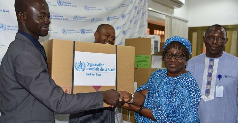 The Chief of Staff at the Ministry of Health, Mr Emmanuel SORGHO, receiving one of the emergency kits from WHO Representative in Burkina Faso, Dr. Alimata J. DIARRA-NAMA