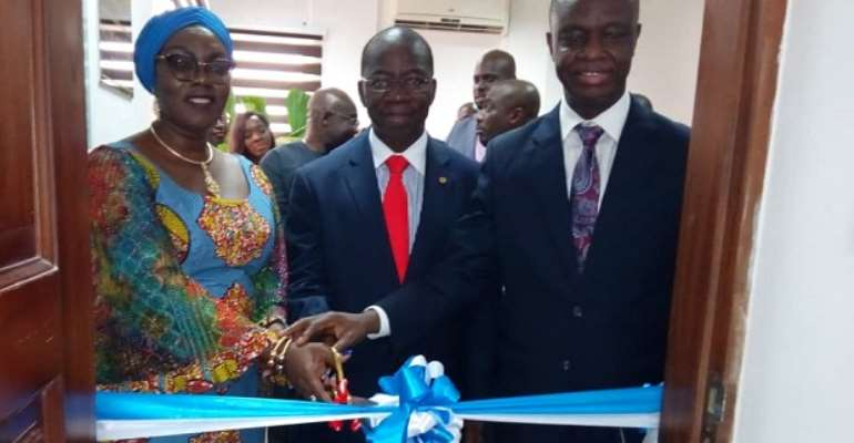 Ursula Owusu-Ekuful assisted by Joe Anokye to cut the tape to symbolize the official opening of the lab