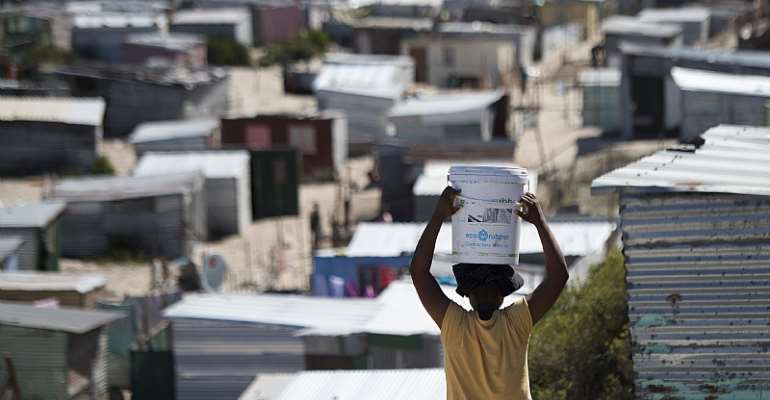A woman carries a bucket of fresh water to an informal settlement in Khayelitsha,Cape Town. - Source: