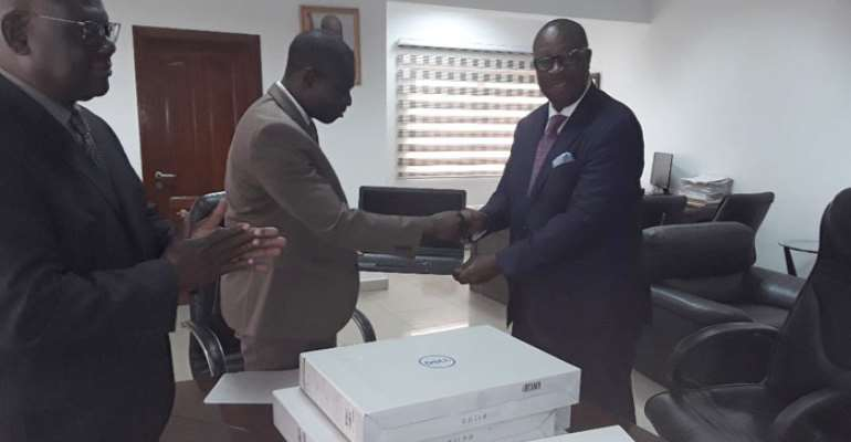 Dr Nortey Oma boe (right) presenting a laptop to Kweku Kwarteng