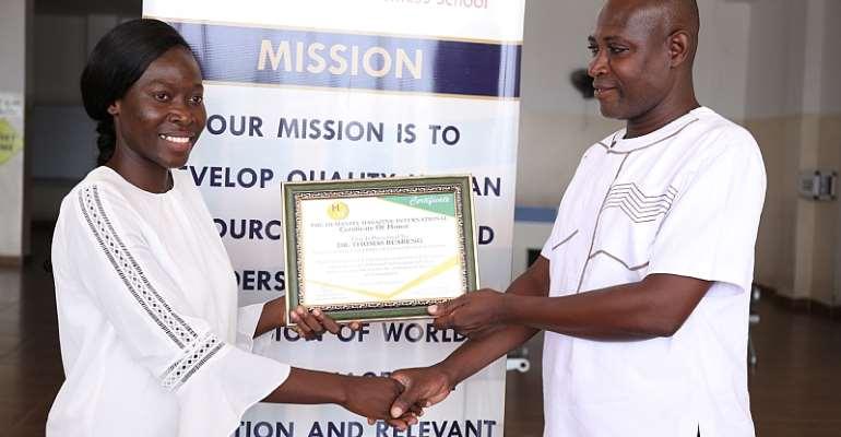 Ms. Jennifer Yeboaa (left) presenting the Humanity award to Dr. Thomas Buabeng