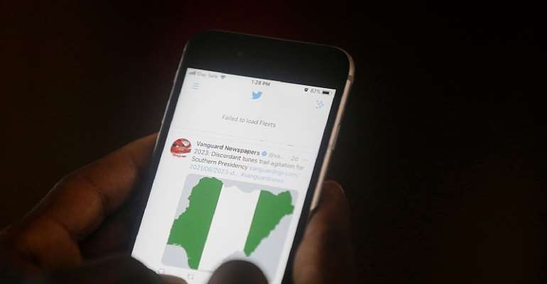 A man uses his mobile phone to read headline news on Twitter in Lagos, Nigeria, on June 7, 2021. Two Nigerian journalists talked to CPJ about the government's ongoing Twitter ban. (AP Photo/Sunday Alamba)