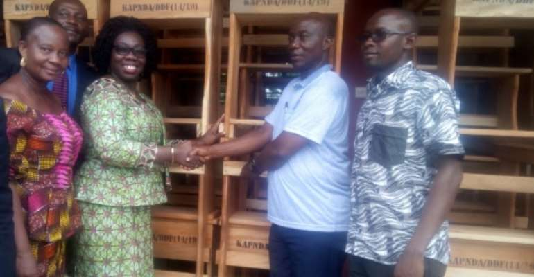 Mr Kena (DCE) presenting the furniture to Mrs Ivy Owusu Asantewaa, GES District Director
