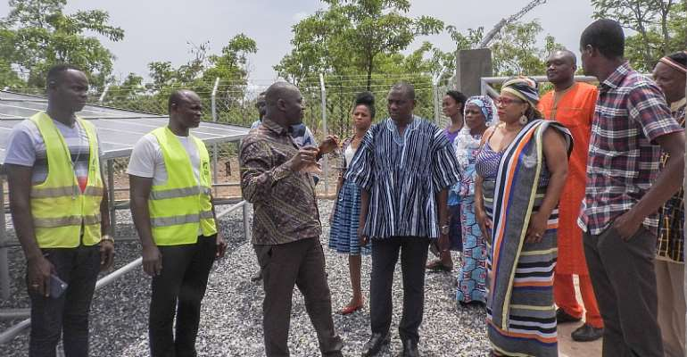Group comprising USAID/Ghana representatives, Chiefs and Global communities representatives admiring both the solar panels and the electricity change over component of the Tuna water system