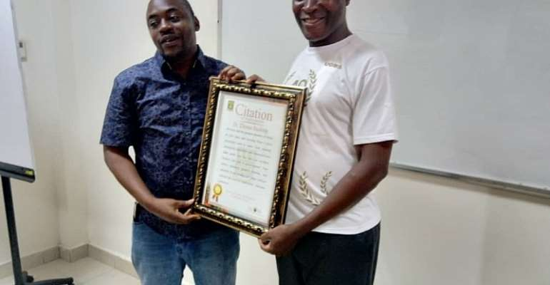 Mr. Yahaya Alhassan (right) presenting a certificate of honour to Dr. Thomas Buabeng