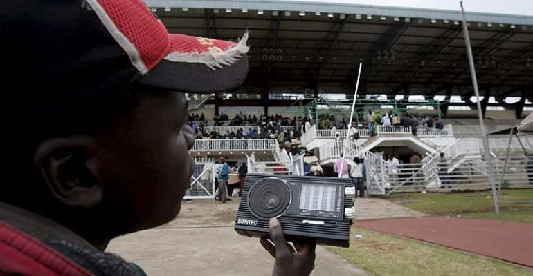 A party agent listens to the radio as electoral officials confirm and tally votes from polling stations  in Nairobi, Kenya in 2007.  - Source: Stephen Morrison/EPA