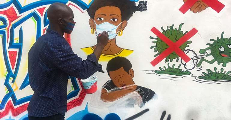 Congolese artist Chris Shongo paints on the outside wall of the Academie des Beaux-Arts in Kinshasa on June 18, 2020.  - Source: