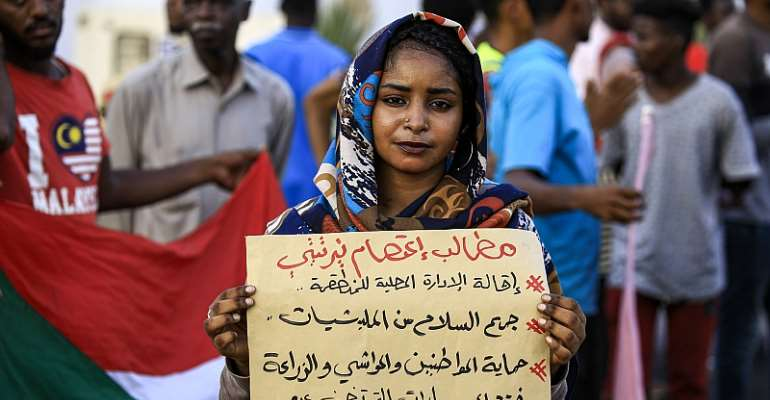 """A demonstrator stands with a sign reading: """"Demands: sack the local authority, disarm militias, protect citizens, cattle, and farmland, and end friction between farmers and shepherds"""", during a protest in Central Darfur.   - Source: Ashraf Shazly/AFP via Getty Images"""