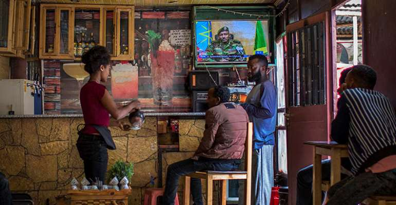 Ethiopians follow the news on television at a cafe in Addis Ababa, Ethiopia Sunday, June 23, 2019. Ethiopian authorities arrested journalist Mesganaw Getachew on August 9 after he filmed outside a court in Addis Ababa. (AP Photo/Mulugeta Ayene)
