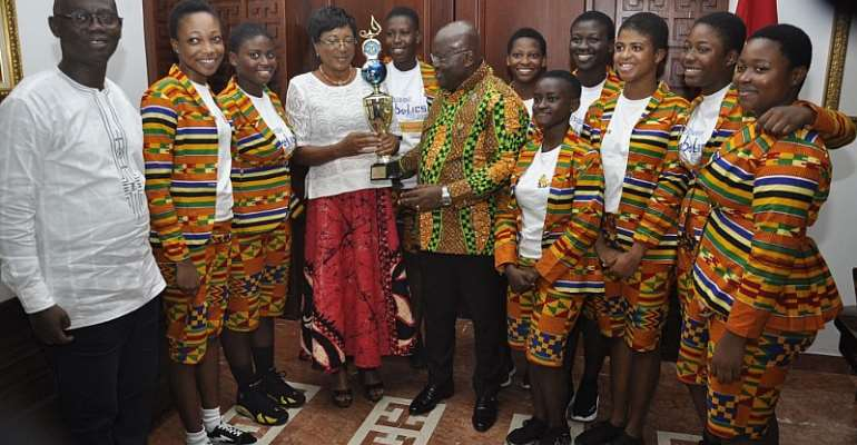 President Nana Addo Dankwa Akufo-Addo receiving a trophy won by the Robotics Team from Mrs Sylvia Isabella Laeryea (4th left). With them are the students