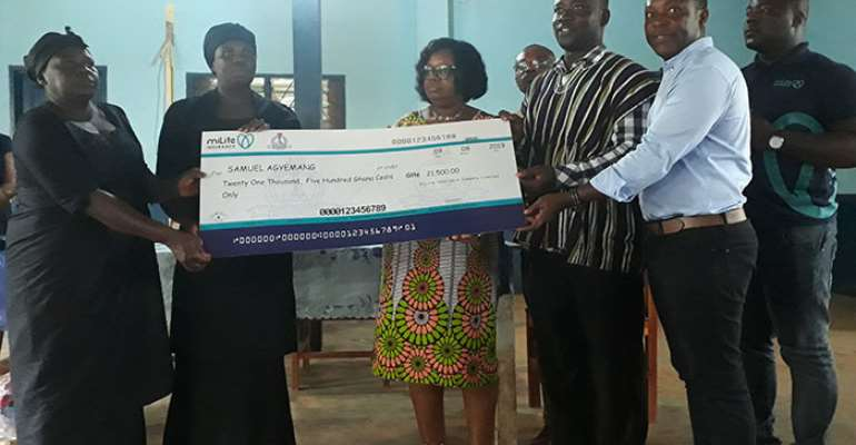 Officials of Milife and GNAT (right) presenting the dummy cheque of GH¢21,500 to the family of the deceased