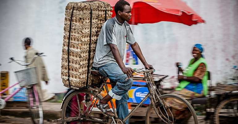 A man rides a bicycle on a market road in Dar es Salaam, Tanzania. Image by Oxford Media Library