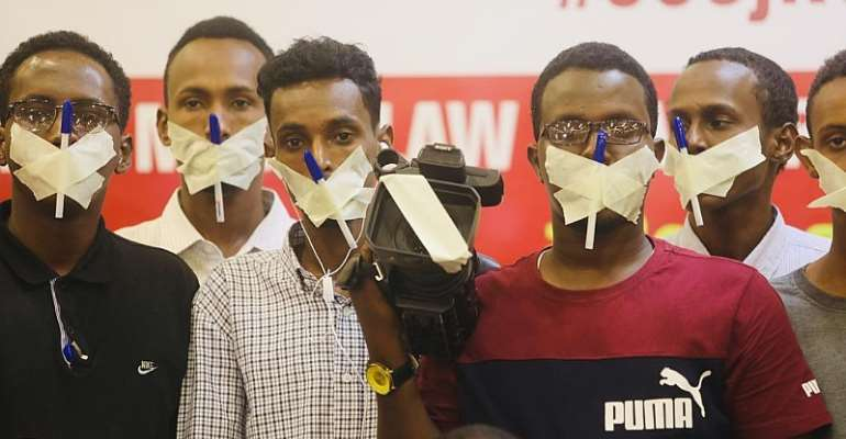 Journalists cover their mouths and cameras with tapes and pens to show protest their disapproval to the draconian media bill which was recently signed into a law. Photo credit: SJS