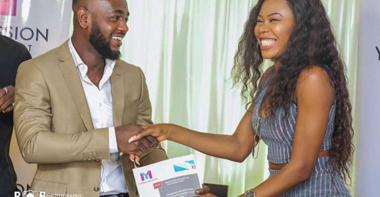 Frimpong Amoako presenting a copy of the contract to Freda Rhymz