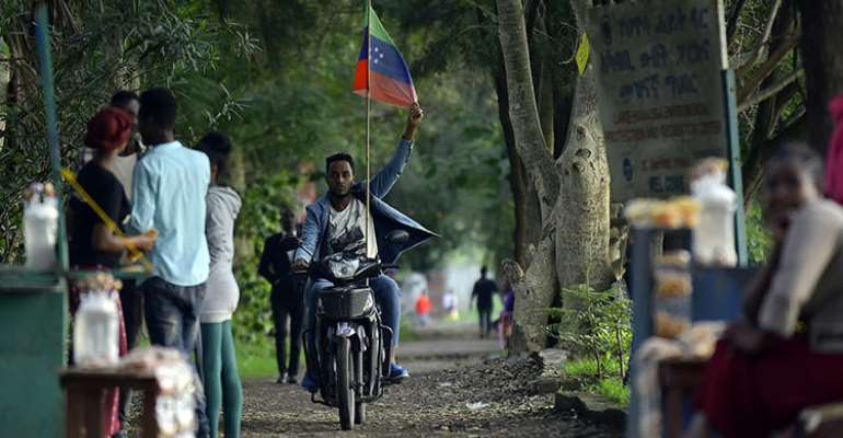 A man rides a motorcycle as young people of the Sidama ethnic group, the largest in southern Ethiopia, celebrate at Hawassa city over plans by local elders to declare the establishment of a breakaway region for the Sidama, in Awasa, July 15, 2019. Authorities arrested three media workers from the Sidama Media Network on July 18. (AFP/Michael Tewelde)