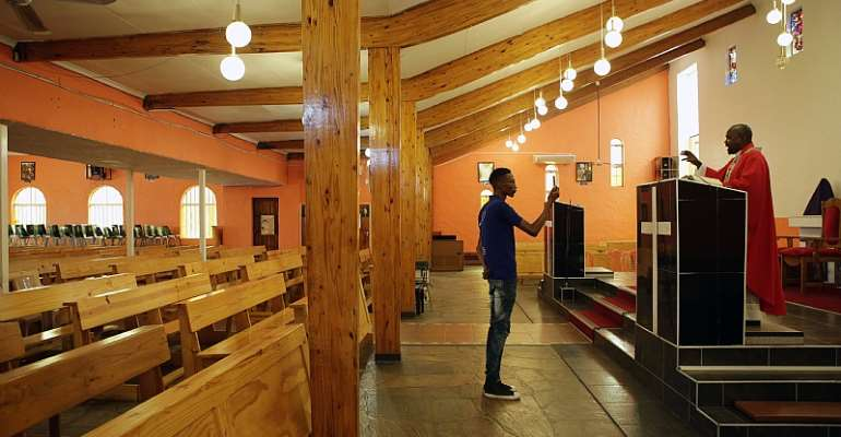 A parishioner records an online mass from an empty church in Mabopane, South Africa, during the COVID-19 lockdown. - Source: PHILL MAGAKOE/AFP via Getty Images