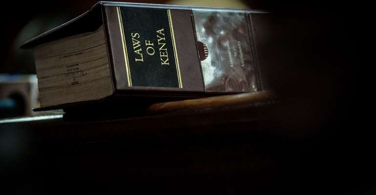 A volume of the Law of Kenya sits on a judge's desk during trial.  - Source: Yasuyoshi Chiba/AFP via Getty Images