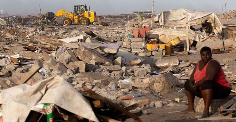 A woman sits at a site in James Town, Accra, demolished in May 2020 to make way for a new fishing port complex.   - Source: Photo by Nipah Dennis/AFP via Getty Images
