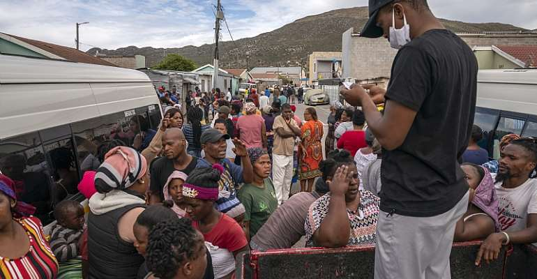 Residents of Masiphumelele informal settlement in Cape Town gather to collect food parcels provided by One South Africa Movement representative.  - Source: EFE-EPA/Nic Bothma