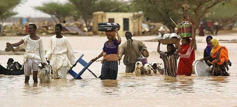 Sudanese people carry their belongings through the flood waters - Source: Isam Al-Haj/AFP via Getty Images