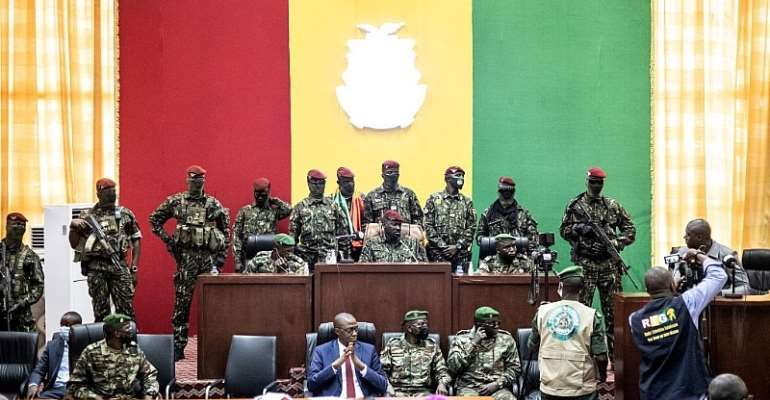 Colonel Mamady Doumbouya (C) and his team of Guinean special forces listen as he holds talks with religious leaders at the People's Palace in Conakry on September 14, 2021.  - Source: JOHN WESSELS/AFP via Getty Images