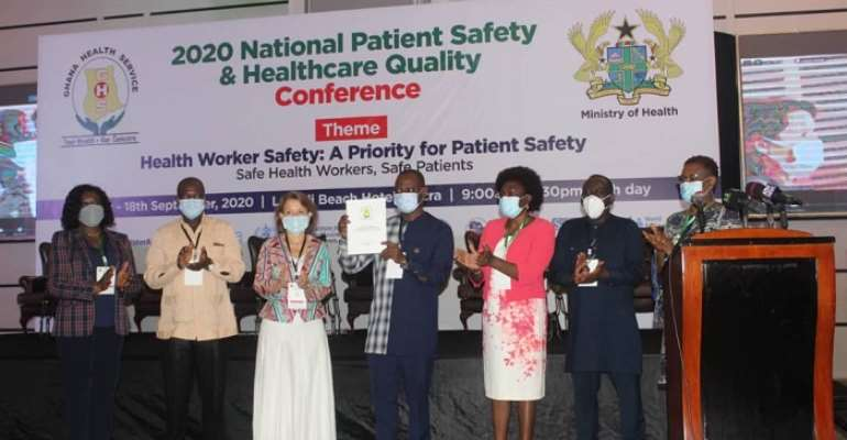 Dr. Kuma-Aboagye (middle) with the new guideline for the implementation of the national healthcare strategy