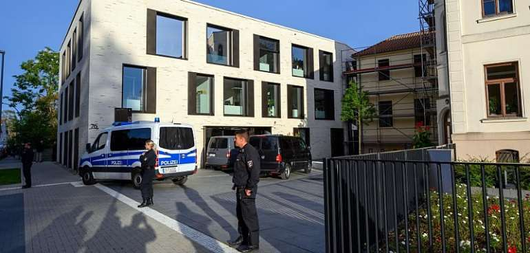 Police officers stand in front of the district office in Wismar